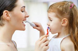 women teaching dental hygiene to kid
